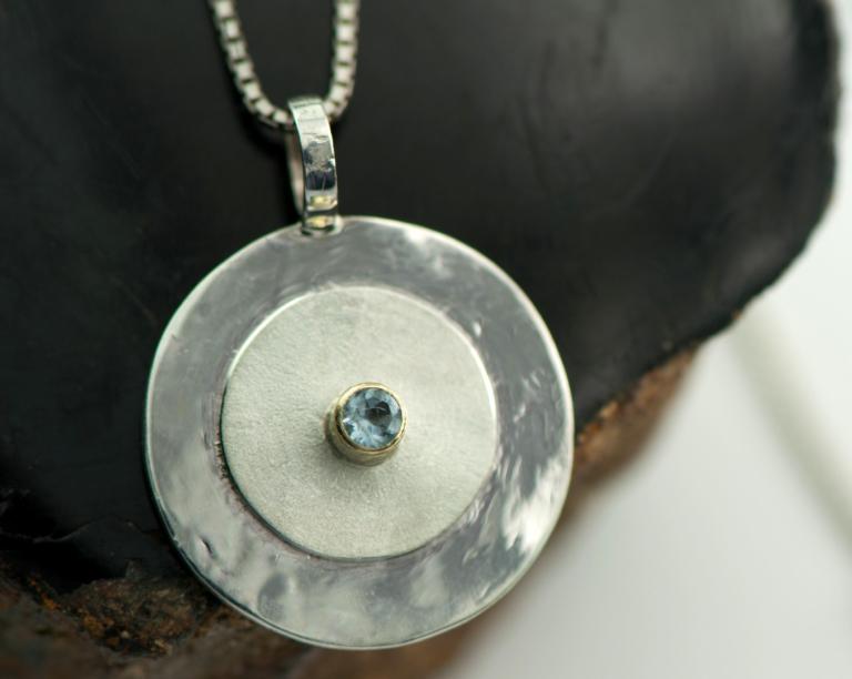 Hanger zilver en aquamarijn, gouden zetrand, gehamerd en gematteerd zilver