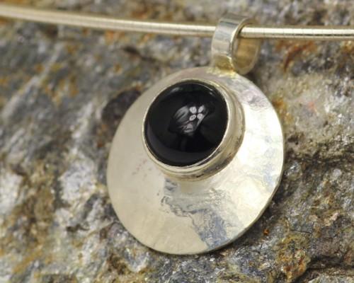 handgemaakte onyxhanger van gehamerd zilver en een ronde gitzwarte onyx.