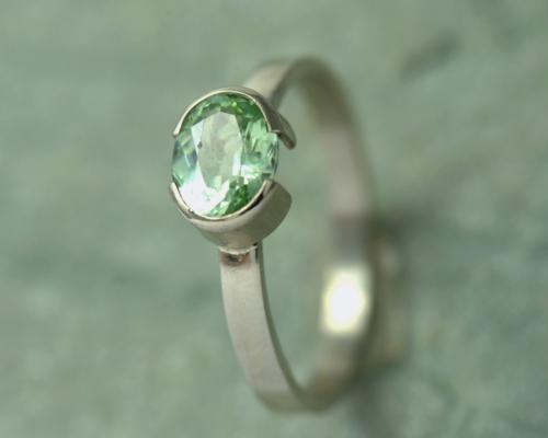 Witgouden ring met mintgroene peridoot: ovale groene edelsteen peridoot is gezet op een witgouden ringband. Halfopen zetting. Handgemaakt.